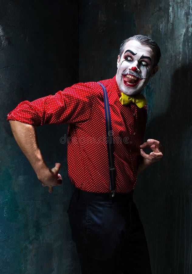 Schrecklicher Clown und Halloween-Thema: Verrückter roter Clown in einem Hemd mit Hosenträgern lizenzfreies stockbild