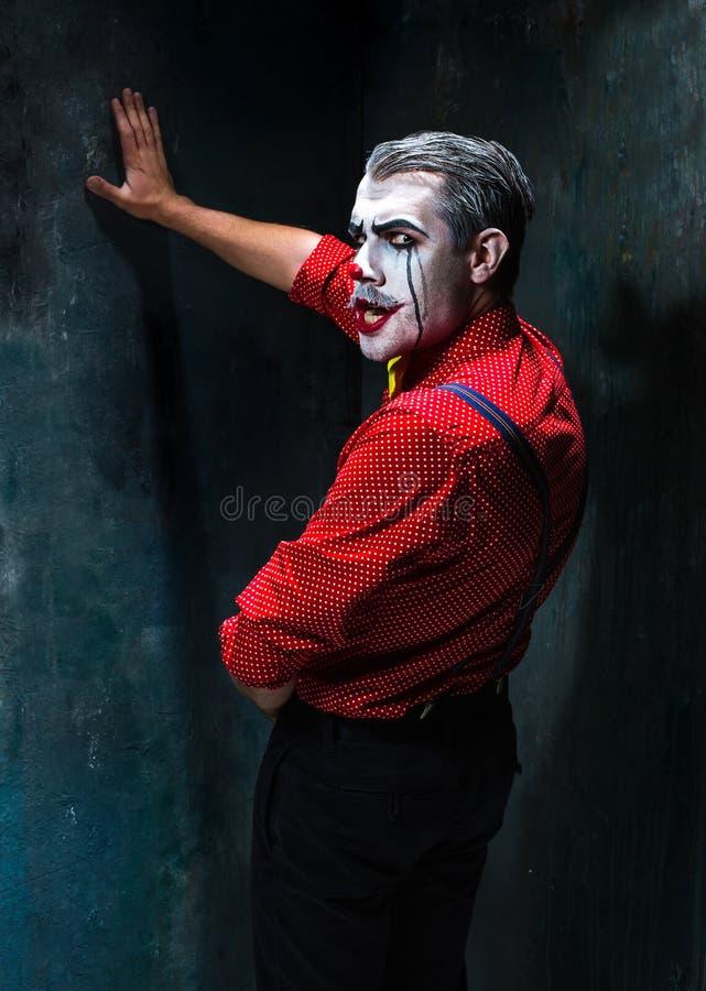 Schrecklicher Clown und Halloween-Thema: Verrückter roter Clown in einem Hemd mit Hosenträgern lizenzfreies stockfoto