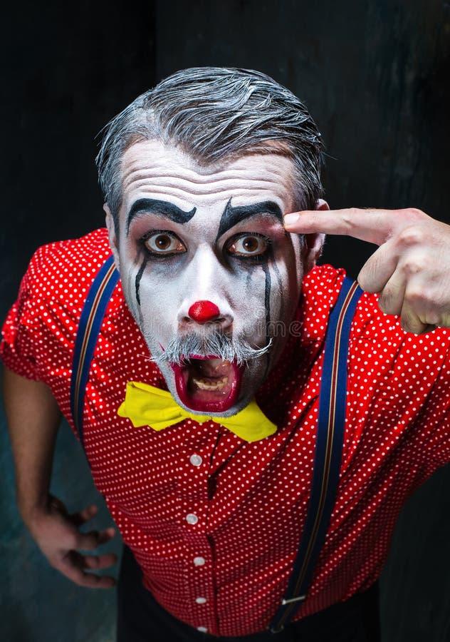 Schrecklicher Clown und Halloween-Thema: Verrückter roter Clown in einem Hemd mit Hosenträgern lizenzfreie stockfotos