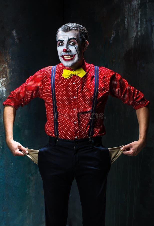 Schrecklicher Clown und Halloween-Thema: Verrückter roter Clown in einem Hemd mit Hosenträgern stockfotos