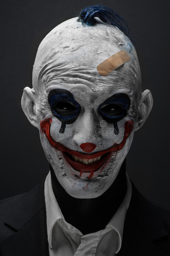 Schrecklicher Clown und Halloween-Thema: Verrückter schrecklicher blauer Clown im schwarzen Anzug lokalisiert auf einem dunklen H lizenzfreies stockfoto