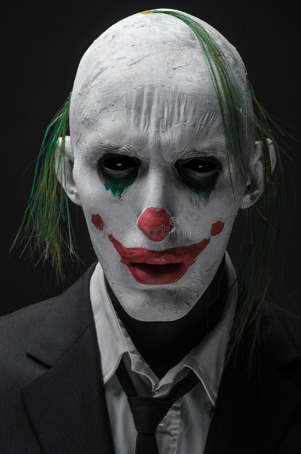 Schrecklicher Clown und Halloween-Thema: Verrückter schrecklicher grüner Clown im schwarzen Anzug lokalisiert auf einem dunklen H lizenzfreies stockfoto
