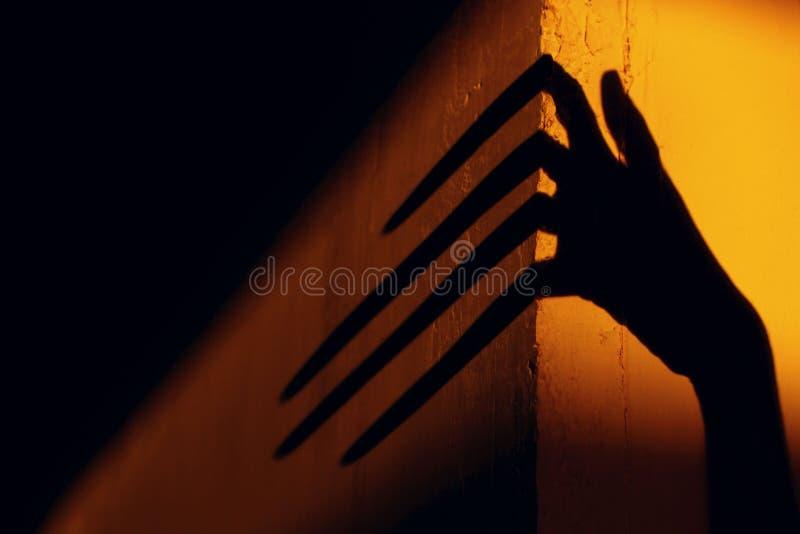 Schrecklicher Schatten entziehen Sie Hintergrund Schwarzer Schatten einer großen Hand auf der Wand stockbild