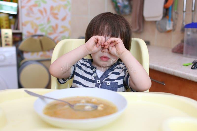 Schreeuwend weinig jongen wil erwten geen soep eten stock afbeelding