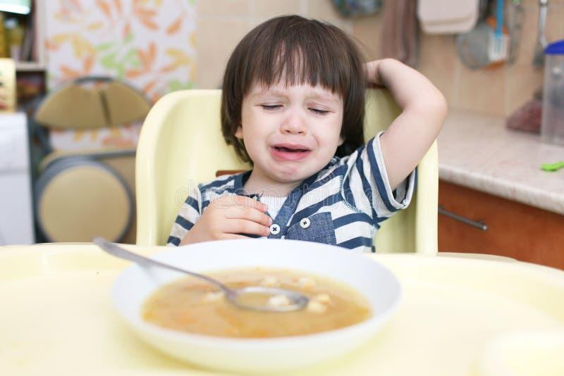 Schreeuwend weinig jongen wil niet eten stock fotografie