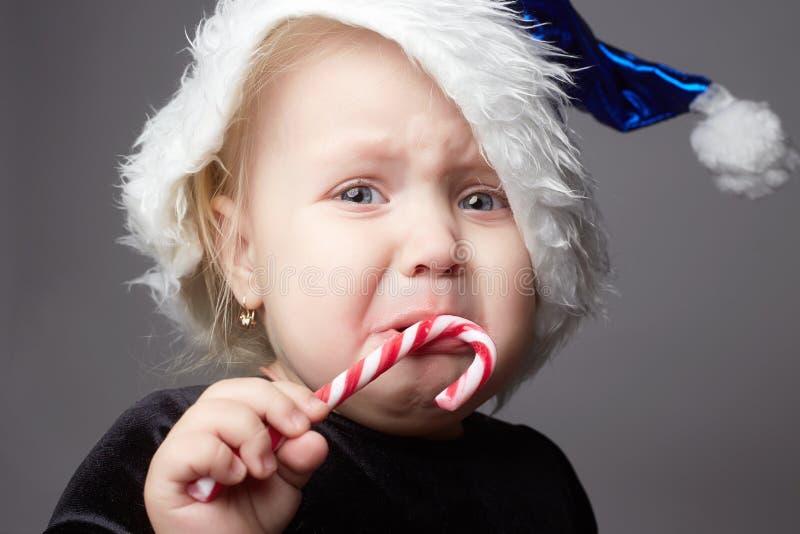 Schreeuwende baby Jong geitje met suikergoed droevig kind in Kerstmistijd stock foto's