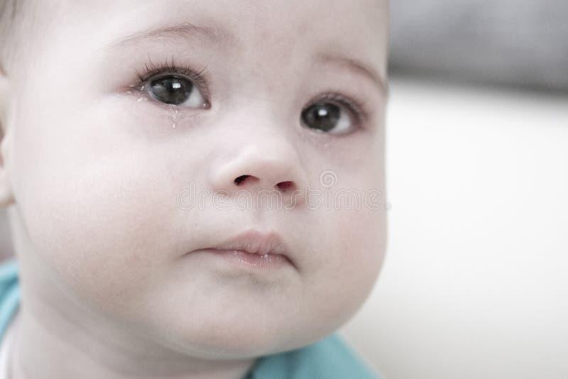 Schreeuwende baby 6 7 maanden, portretclose-up Het droevige gezicht van een kind met scheuren in zijn ogen, baby scheurt de jonge stock foto