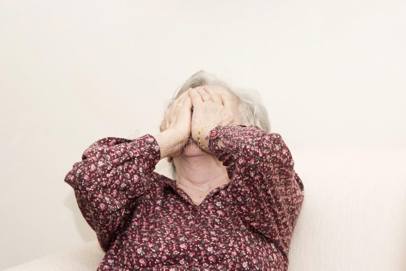 Schreeuwende oude vrouwenzitting stock foto