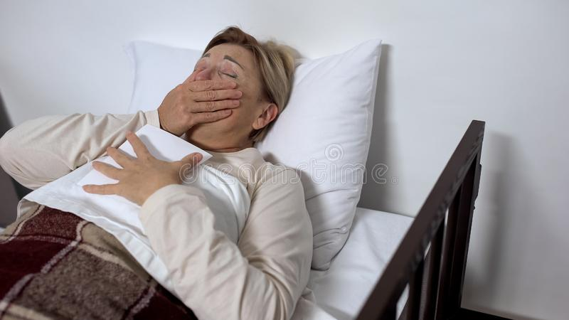 Schreeuwende zieke vrouw die familiefoto koesteren, die in het ziekenhuisbed liggen, waardevol geheugen royalty-vrije stock fotografie