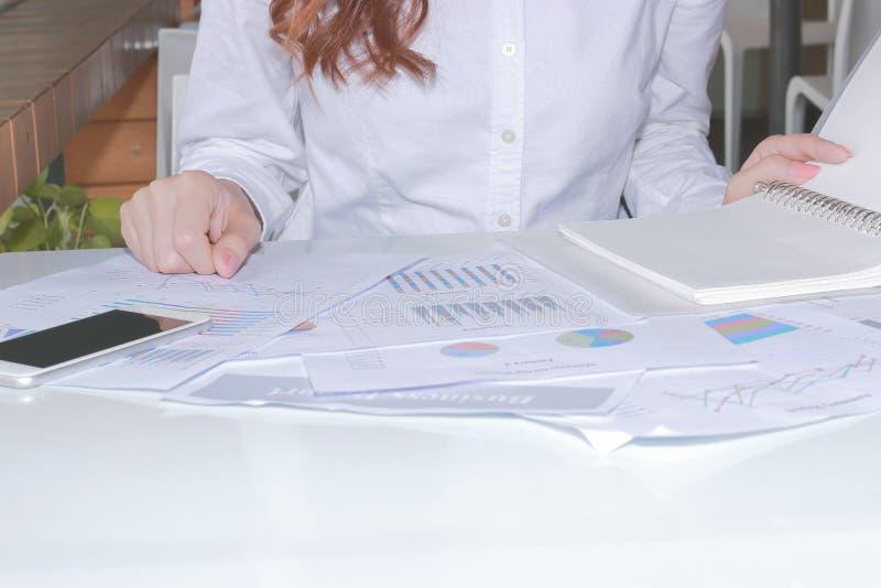 Schreibarbeit oder Diagramme auf dem Schreibtisch im Büro mit Angestelltem stockbilder