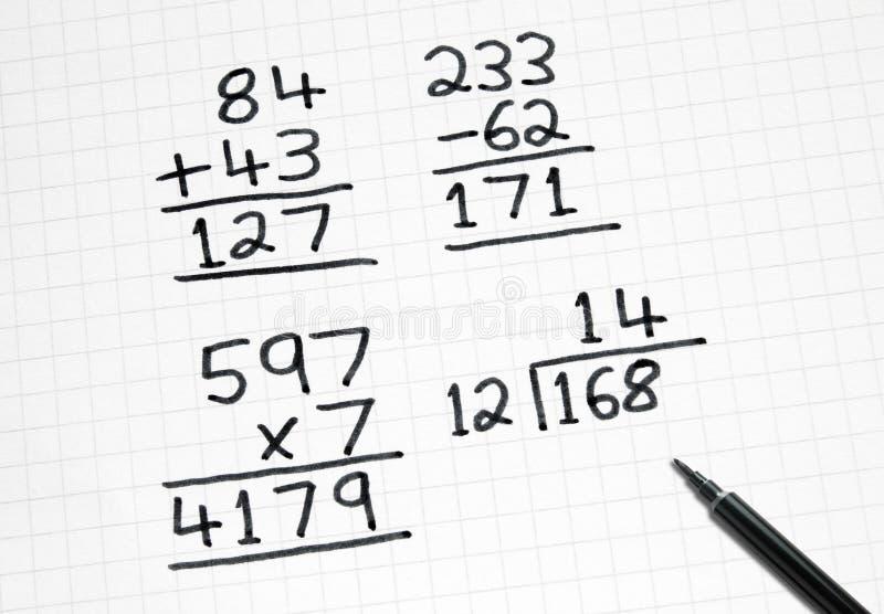 Schreiben der einfachen Mathesummen auf quadratisches Papier. stockfotos