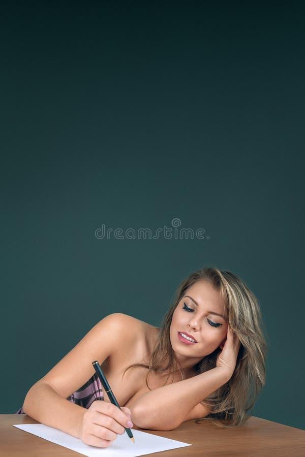 Schreiben der jungen Frau auf Papierseite lizenzfreies stockfoto