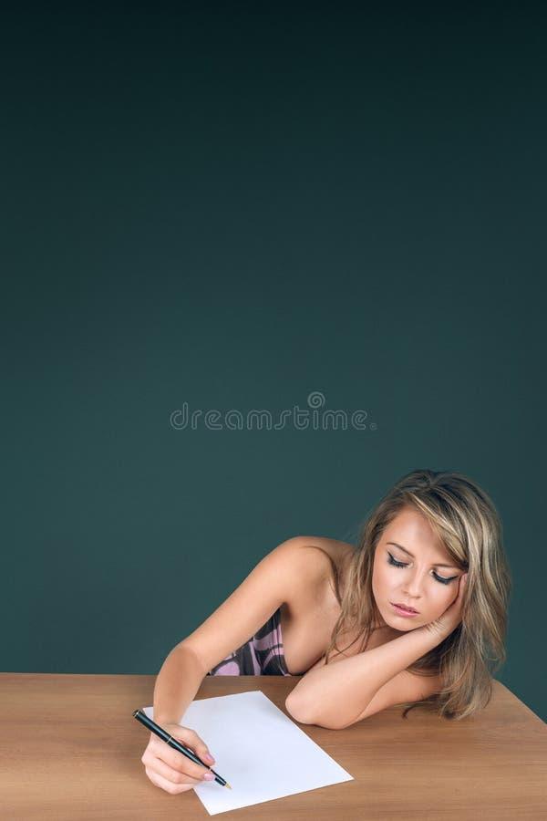 Schreiben der jungen Frau auf Papierseite stockfoto