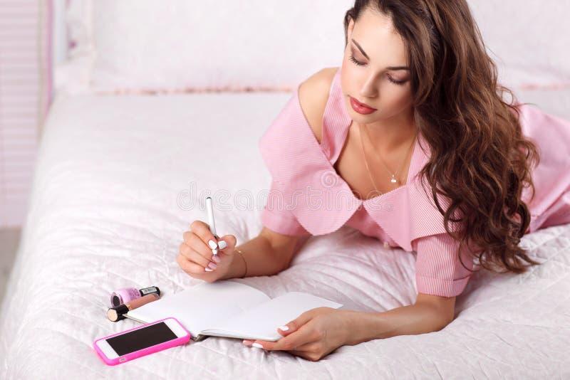Schreiben der jungen Frau in ihrem freien Raum des Tagebuchs lizenzfreie stockfotografie