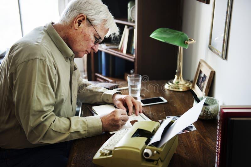 Schreiben des älteren Mannes auf Schreibmaschine lizenzfreie stockfotos