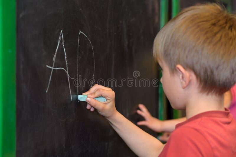 Schreiben des kleinen Jungen auf einer Tafel lizenzfreies stockbild