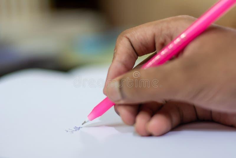Schreiben mit Stift- und Papiernahaufnahme der Hand stockfoto