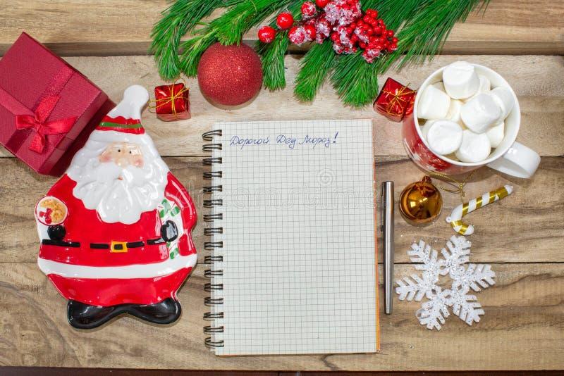 Schreiben Santa Claus eines Briefes auf einem hölzernen Hintergrund mit Weihnachtsgeschenken und -dekorationen, eine Platte in Fo lizenzfreie stockfotografie