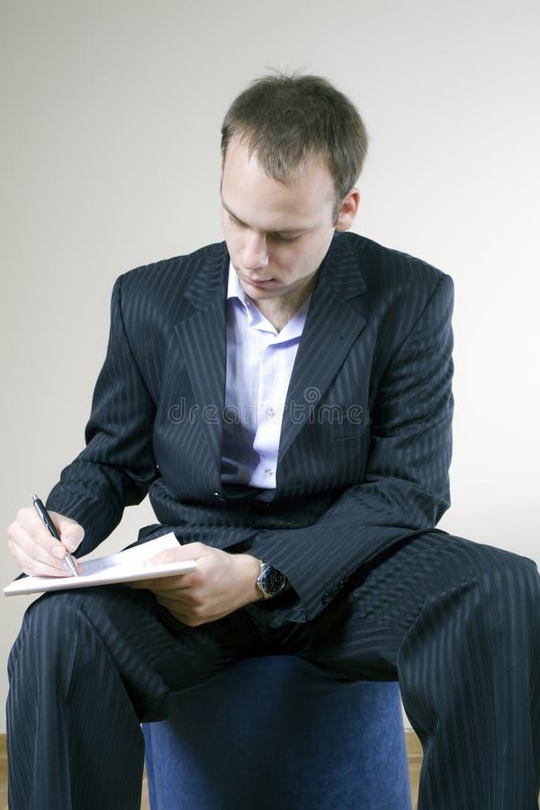 Schreiben in sein Notizbuch stockbild