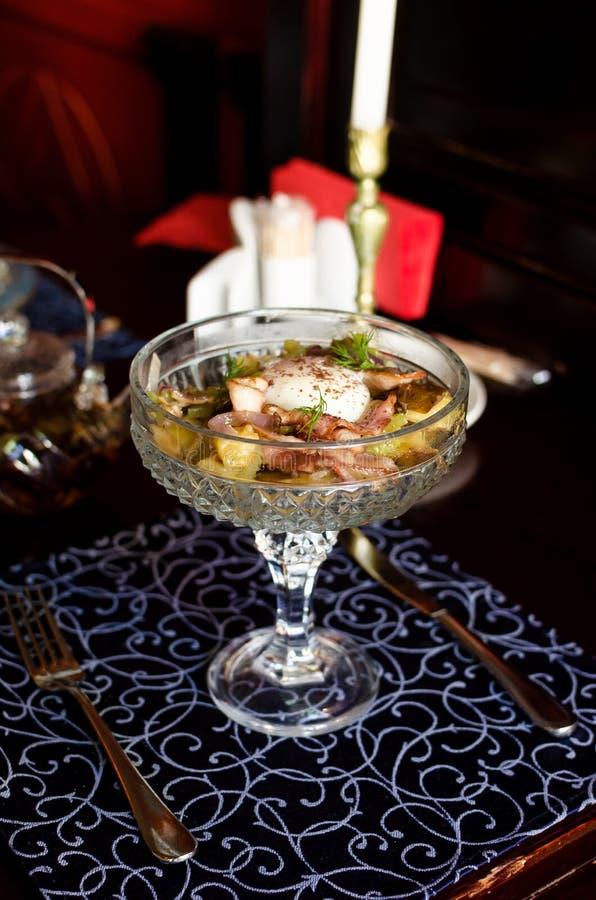Schreiben Sie ` s Salat mit dem Ei, das in einem schönen Weinleseteller pochiert wird stockfotografie