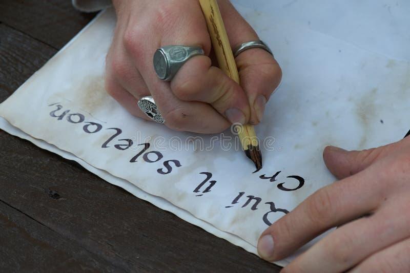 Schreiben von Kalligraphiestiften auf altes Blatt Papier lizenzfreie stockfotografie