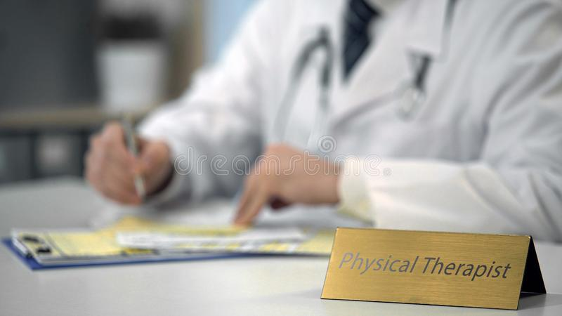 Schreibenbericht des körperlichen Therapeuten über die Laptop-Computer, Krankenblätter führend lizenzfreie stockfotos