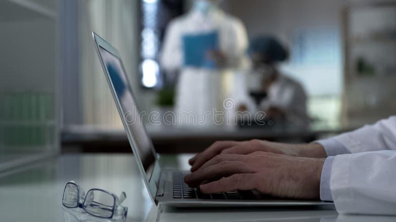 Schreibenexperiment des Wissenschaftlers resultiert auf dem Laptop und arbeitet am Projekt im Labor stockfoto