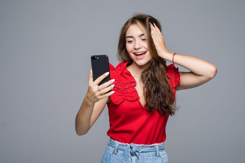 Schreibenmitteilung der jungen Frau auf Smartphone schönes lächelndes Mädchen, das seinen Handy, grauen Studiohintergrund verwend lizenzfreie stockbilder