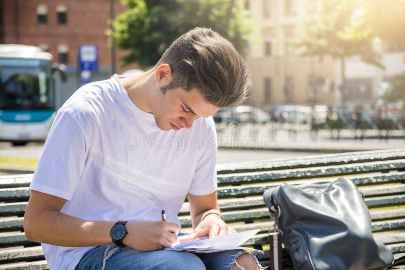 Schreibensanmerkungen des jungen Mannes über Notizblock in der Stadt lizenzfreie stockfotografie