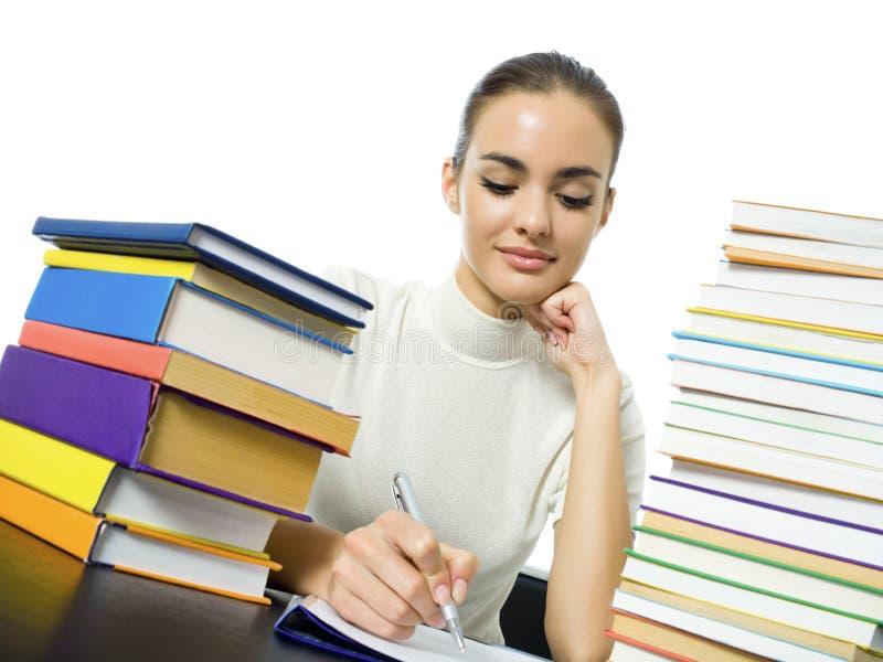 Schreibensfrau mit Lehrbüchern stockfoto