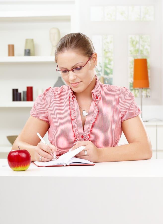 Schreibenstagebuch der jungen Frau stockbild