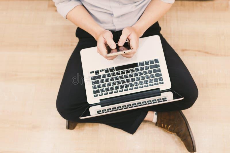 Schreibentextnachricht des Draufsichtmannes an seinem intelligenten Telefon während sittin stockbilder