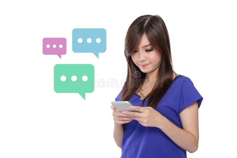 Schreibentextnachrichten des Mädchens mit Smartphone, bunte Schwätzchenblasen, lokalisiert auf Weiß lizenzfreie stockfotos