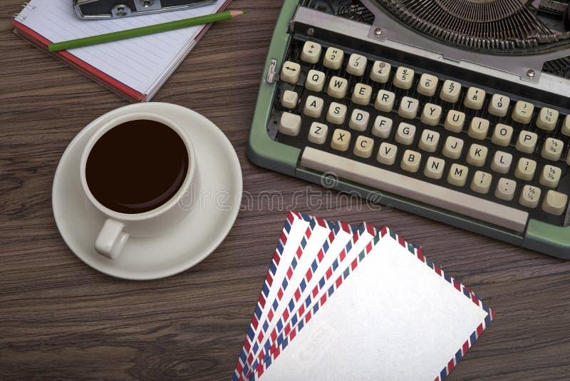 Schreibmaschine auf dem alten Holzschreibtisch mit Kaffeetasse und Notizbuch-Top-Ansicht stockfotos