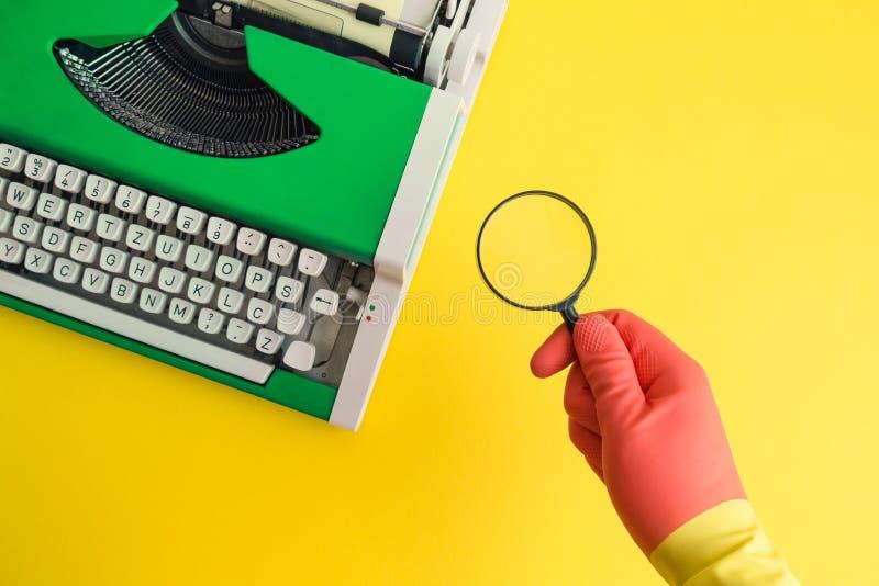 Schreibmaschine und Hand, die Lupe gegen gelben Hintergrund halten lizenzfreie stockfotografie