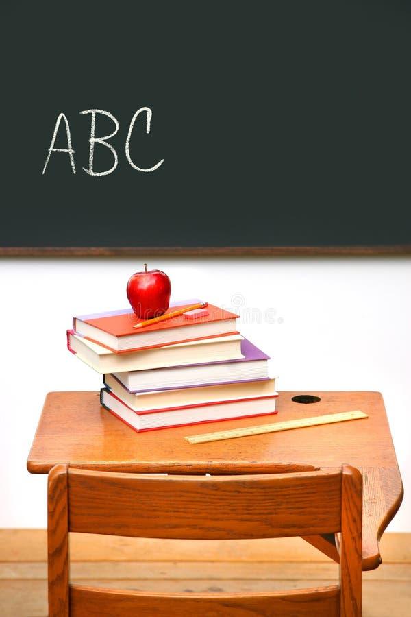 Schreibtisch der alten Schule mit einem Stapel Büchern stockfoto