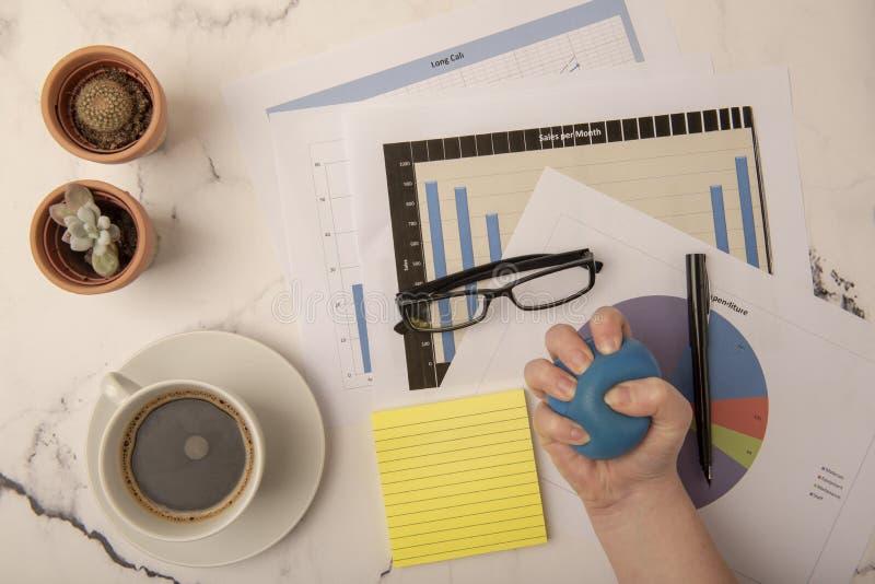 Schreibtisch mit der Hand, die Druckball zusammendrückt stockbild