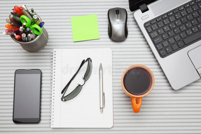 Schreibtisch mit Laptop mit Geschäftszubehör und Tasse Tee stockfoto