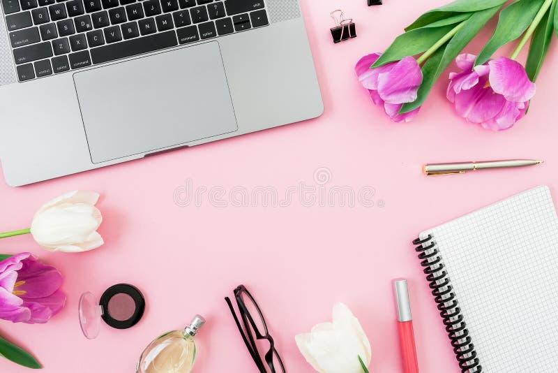 Schreibtisch mit Laptop, Tulpenblumen, Kosmetik, Gläsern und Stift auf rosa Hintergrund Flache Lage Beschneidungspfad eingeschlos stockfotografie