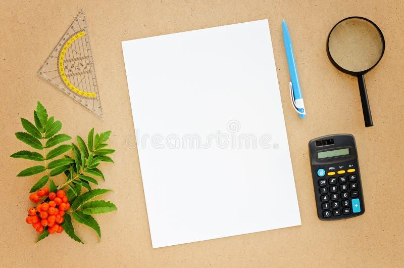 Schreibtisch mit Papier, Stift, Taschenrechner, Vergrößerungsglas und Machthaber stockfotografie