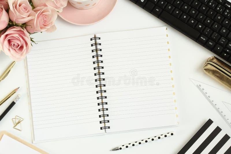 Schreibtisch mit rosa Blumen, leerem Notizbuch und Computer stockfotos