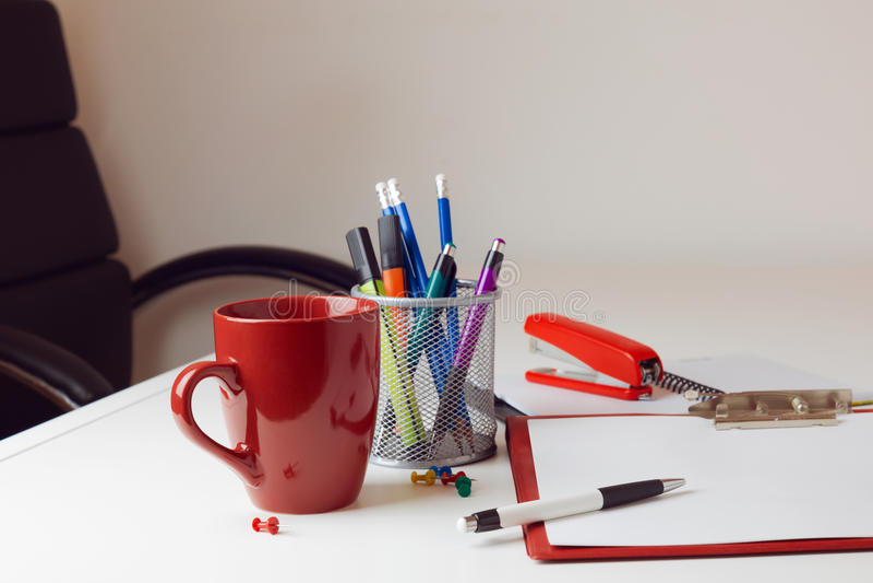 Schreibtisch mit verschiedenen Einzelteilen einschließlich Kaffeetasse, Stuhl und stationäres stockfotos