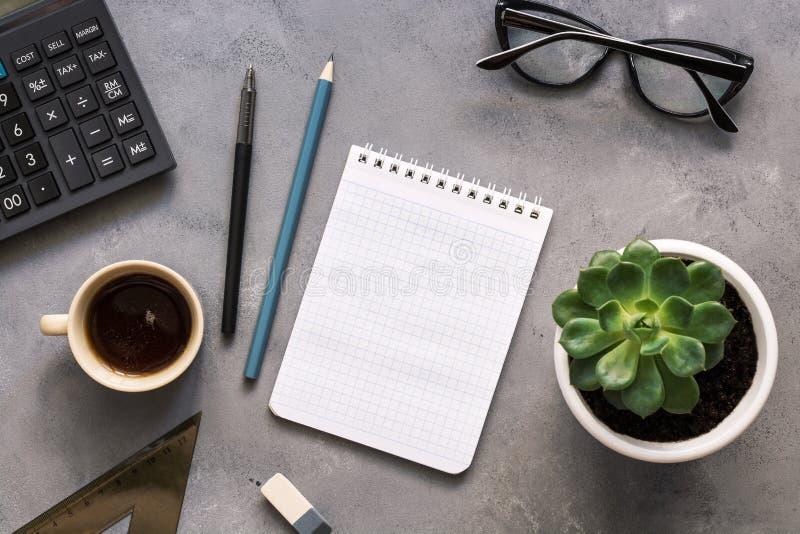 Schreibtisch, Notizbuch, Taschenrechner, Machthaber, Stift, Bleistift, Gläser, Blume, Kaffee auf einem grauen Hintergrund Die Ans stockfotografie