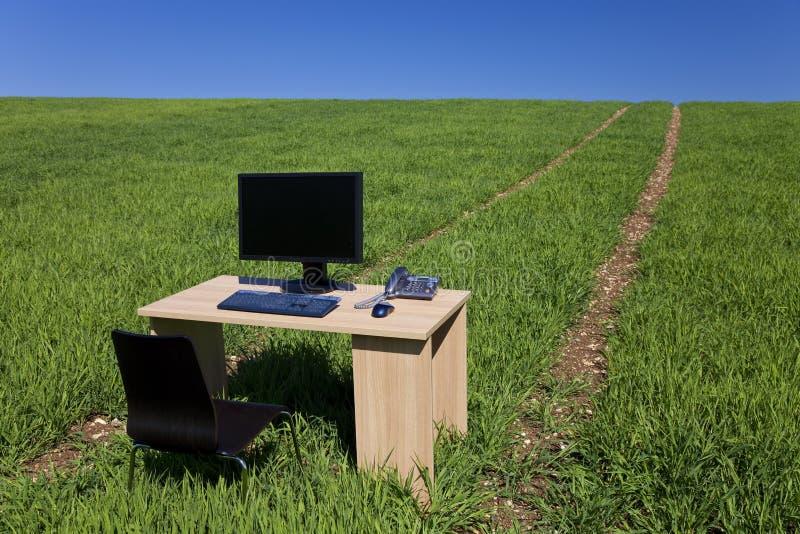 Schreibtisch, Telefon u. Computer auf dem grünen Gebiet mit Pfad stockfoto