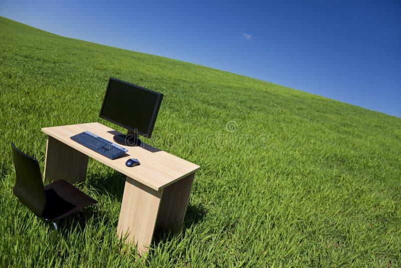 Schreibtisch und Computer auf dem grünen Gebiet mit blauem Himmel stockbilder