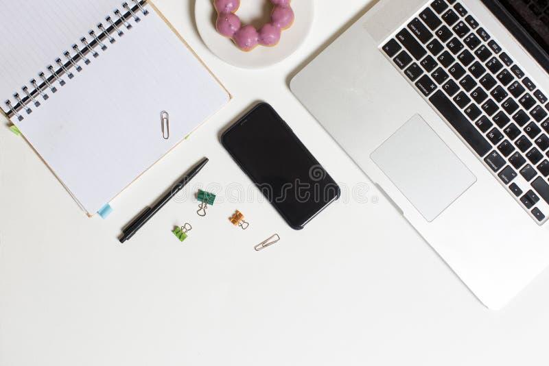 Schreibtischarbeitsplatz Laptop-Computer, Smartphone, Schaumgummiring und Anmerkung über weißen Hintergrund stockfoto
