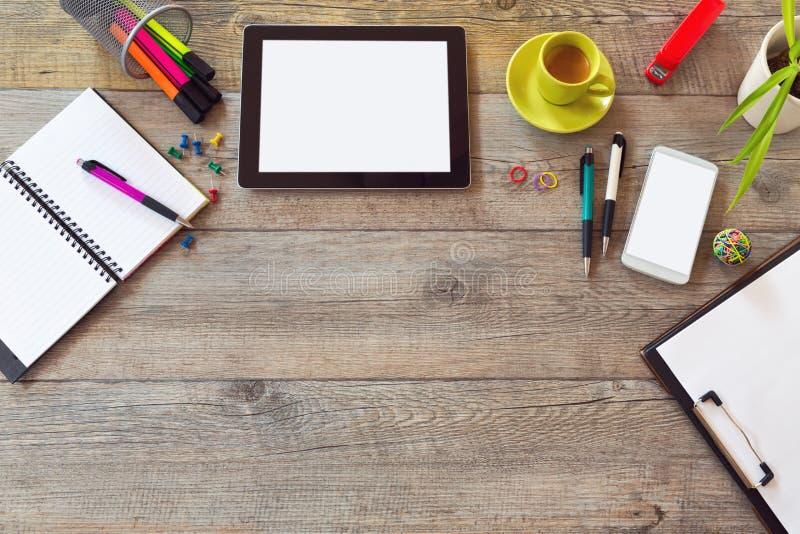 Schreibtischspott herauf Schablone mit Tabelle, intelligentem Telefon, Notizbuch und Tasse Kaffee stockfotografie