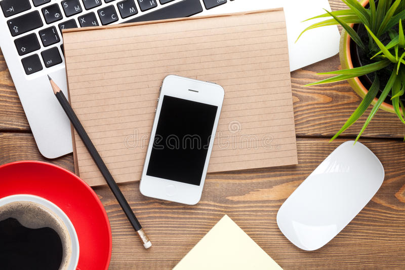 Schreibtischtabelle mit Computer, Versorgungen, Kaffeetasse und Blume lizenzfreie stockfotos