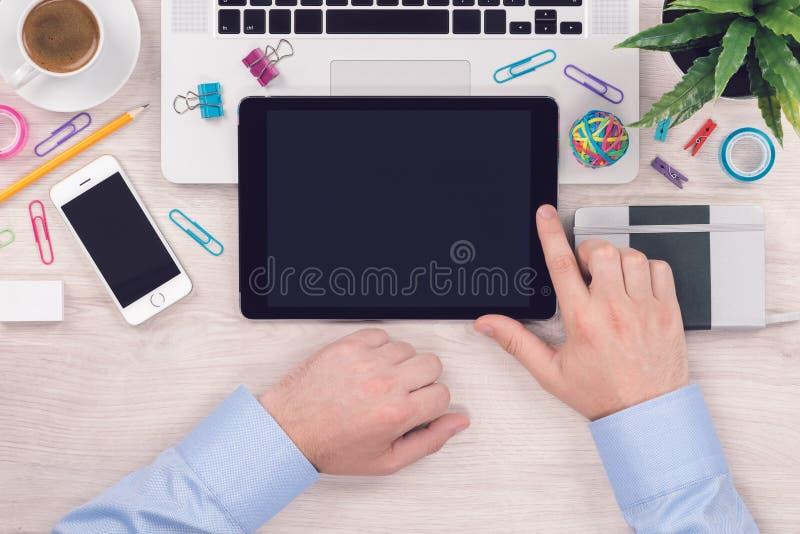 Schreibtischtabellenarbeitsplatz mit digitalem Tabletten-PC und bemannt Hände auf ihm Draufsichtebenenlage lizenzfreie stockfotos