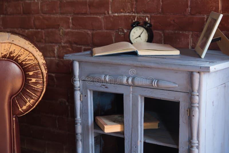 Schreibtischuhr mit einem Buch auf einem hölzernen Schrank gegen einen Backsteinmauerhintergrund lizenzfreie stockfotos